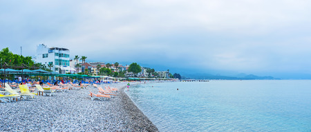 KEMER, TURKEY - MAY 5, 2017: The rainy sky over the central Moonlight beach of Kemer, tourists relax on the sun beds and enjoy the swimming, on May 5 in Kemer.