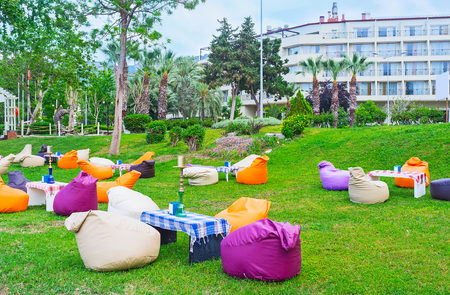 The lovely outdoor lounge cafe with colorful bean bag chairs and shishas on tables, Kemer, Turkey.