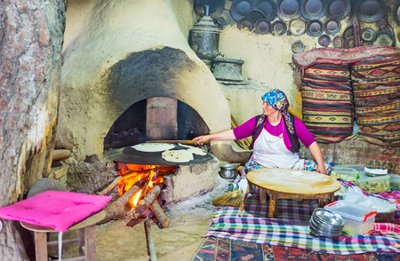 KEMER, TURKEY - MAY 5, 2017: The interior of traditional village kitchen with griddle, heated by wood, standing in clay oven, the cook prepares gozleme - Turkish flatbread with toppings, on May 5 in Kemer.