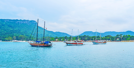 city park boat house: Three ships in harbor of Moonlight beach, surrounded by emerald Taurus mountains with lush pine forests, Kemer, Turkey. Stock Photo