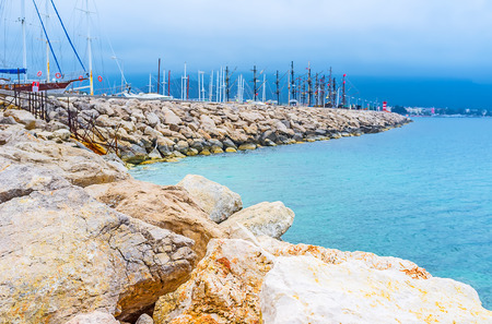 city park boat house: The sails of the tourist ships and yachts are seen behind the stone pier of Marina in Kemer, Turkey.