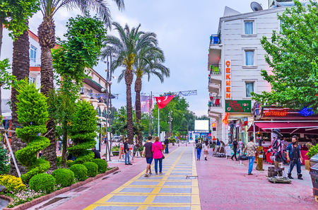 KEMER, TURKEY - MAY 5, 2017: The Munir Ozkul Liman street with tourist shops and numerous cafes has the scenic flower bed in the middle with lush green plants and trees, on May 5 in Kemer.