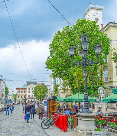 LVOV, UKRAINE - MAY 16, 2017: The scenic old style streetlight in the Market Square (Ploshcha Rynok) with cafe around the statue of Greek goddess Diana and the tower of City Hall on background, on May 16 in Lvov. Editorial