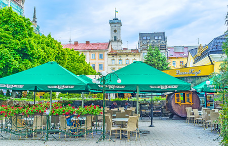 LVOV, UKRAINE - MAY 16, 2017: The summer cafe in Ivan Pidkova square, surrounded by lush greenery, with old mansions and tower of City Hall on background, on May 16 in Lvov.
