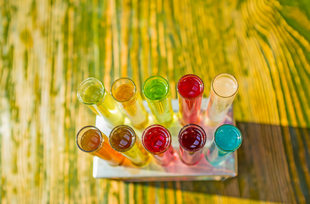 The test tubes with alcohol spirits on the old wooden background, Lvov, Ukraine. Stock Photo