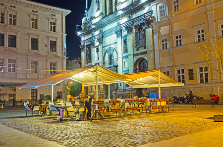 LVOV, UKRAINE - MAY 16, 2017: The cozy outdoor terrace of the restaurant is the perfect place to spend the evening with a view on medieval facade of Garrison Church of St Peter and Paul, on May 16 in Lvov. Editorial