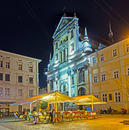 LVOV, UKRAINE - MAY 16, 2017: The huge Garrison Church of St Peter and Paul behind the covered summer terrace of the local cafe, on May 16 in Lvov. Editorial