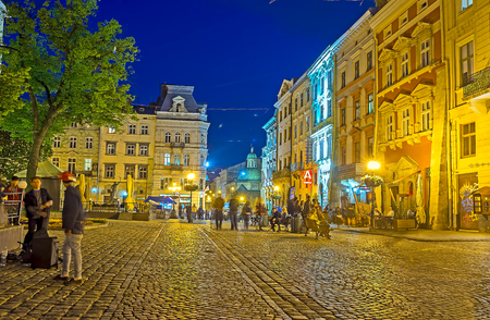 LVOV, UKRAINE - MAY 16, 2017: The Market Square (Ploshcha Rynok) in bright lights, cafes and bars welcomes the visitors with lounge music and cozy terraces, on May 16 in Lvov.
