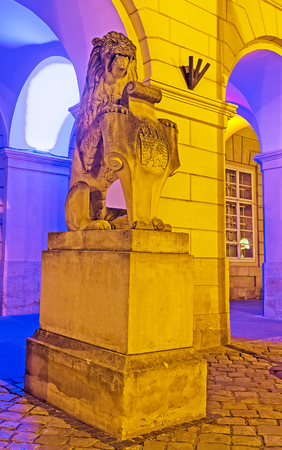 The sculpture of sitting roaring lion - the city symbol with the coat of arms of Lvov (town of lion), at the entrance to the City Hall in Market Square in bright night lights, Ukraine. Editorial