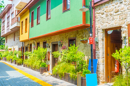 The old narrow streets of Kaleici occupied with scenic cottages and decorated with green plants in tubs, Antalya, Turkey.