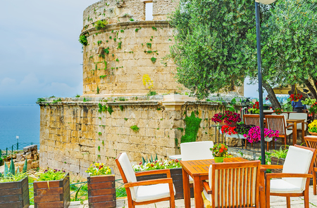 The wooden tables and chairs of the cozy outdoor restaurant next to the Hidirlik Tower - the antique landmark, preserved since the times of Romans, Kaleici, Antalya, Turkey.