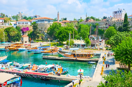 ANTALYA, TURKEY - MAY 6, 2017: The old marina is the best place for the pleasant walk, watching the moored ships, preserved city walls, scenic mansions and relax in shady park, on May 6 in Antalya. Editorial