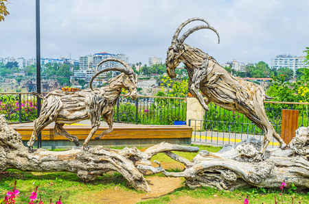 The wooden sculpture in Mermerli park depicts the fight of ibexes, Antalya, Turkey. Stock Photo