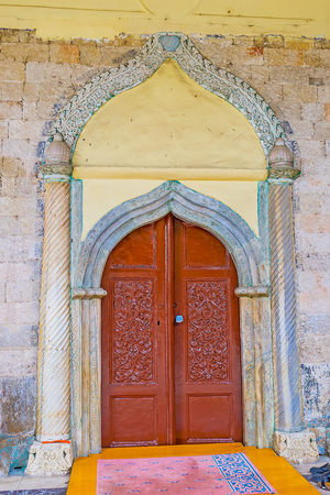 ANTALYA, TURKEY - MAY 6, 2017: The entrance door of Aladdin Mosque decorated with carved stone details, on May 6 in Antalya. Editorial