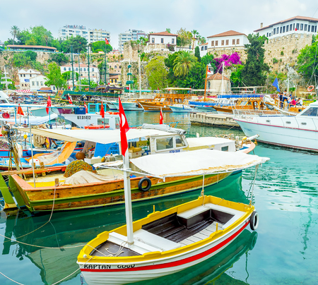 ANTALYA, TURKEY - MAY 6, 2017: The small fishing boats in old marina are neighbor with the pirate galleons and yachts, on May 6 in Antalya.