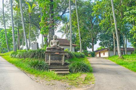 The old stone statue of Meditating Lord Buddha in garden next to the Gadaladeniya Vihara Buddhist Temple, Pilimathalawa, Sri Lanka