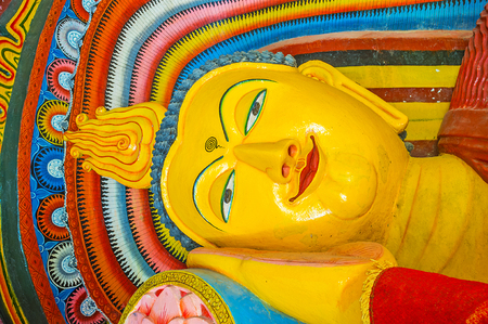 PAMUNUWA, SRI LANKA - NOVEMBER 29, 2016: The face ofReclining Lord Buddha in Pamunuwa Temple, surrounded by colorful traceries, on November 29 in Pamunuwa.