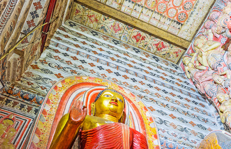 indo: UDUNUWARA, SRI LANKA - NOVEMBER 29, 2016: The ceiling and walls of Lankathilaka Vihara covered with fine floral patterns, neighboring with ancient sculptures of Lord Buddha, on November 29 in Udunuwara.
