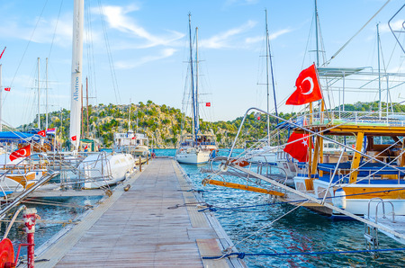 KEKOVA, TURKEY - MAY 7, 2017: The walk along the pier of port between tourist yachts, on May 7 in Kekova Editorial