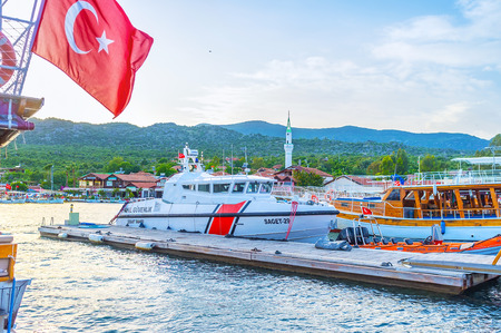 KEKOVA, TURKEY - MAY 7, 2017: The bulky modern boat of coast guard moored among wooden tourist yachts, on May 7 in Kekova