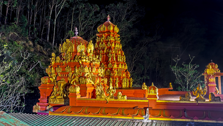 The brightly illuminated vimana and shikhara towers with golden sculptures are seen in dark night, Seetha Amman Hindu Temple, Nuwara Eliya, Sri Lanka. Stock Photo