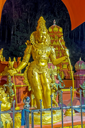 The golden statue of Rama with bow and arrow in frontage of Seetha Amman Temple in Nuwara Eliya, Sri Lanka.