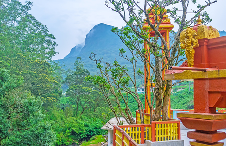 The tower of Seetha Amman Temple behind the tree, surrounded by foggy mountains, Nuwara Eliya, Sri Lanka.