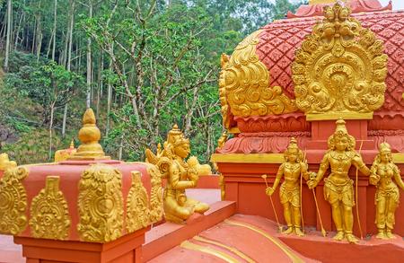 The golden sculptures of Hindu gods Rama, Sita and Lakshmi at the red vimana tower of Seetha Amman Temple, located in Seetha Eliya village, Nuwara Eliya, Sri Lanka.