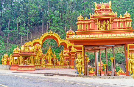 The scenic architecture and bright colors of Seetha Amman Temple with the coniferous forest on the background, Nuwara Eliya, Sri Lanka.