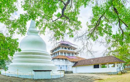 The shade of Bo Tree is the best place to relax and enjoy the beauty of the ancient Lankathilaka Vihara with white Stupa on the foreground, Uduruwana, Sri Lanka.