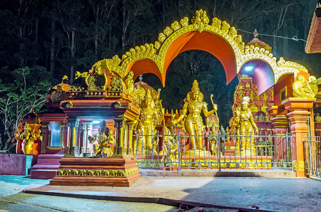 The tiny niche of monkey-headed deity Hanuman with the scenic arch, covering Rama, Seetha and Lakshmana shrine at the Seetha Amman Temple in evening lights, Nuwara Eliya, Sri Lanka.