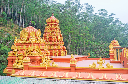 The bright red towers (vimanan and shikhara) of Hindu Seetha Amman Temple (Sita Temple), decorated with golden sculptures of deities and relief patterns, Nuwara Eliya, Sri Lanka.
