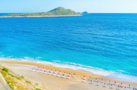 Kaputas beach offers comfortable sunbeds, sandy beach and relax waves of Mediterranean sea, Kalkan, Turkey