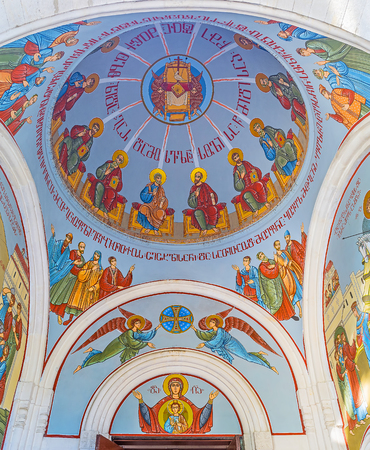 TBILISI, GEORGIA - JUNE 2, 2016: The cupola of Georgian Orthodox Kashveti Church of St George covered with colorful murals with the Saints and Georgian inscriptions, on June 2 in Tbilisi.