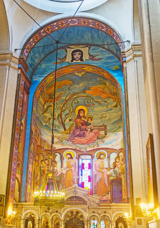 TBILISI, GEORGIA - JUNE 2, 2016: The prayer hall of Orthodox Kashveti Church of St George, the apse decorated with murals with the carved stone iconostasis on the foreground, on June 2 in Tbilisi.