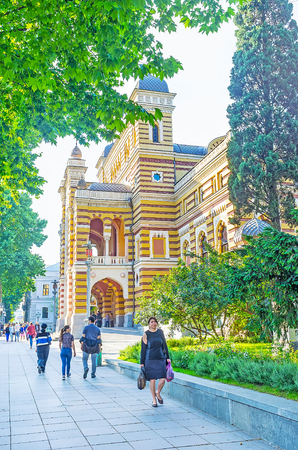 TBILISI, GEORGIA - JUNE 2, 2016: The walk along the shady Rustaveli Avenue with the view on the porch of the Opera and Ballet Theater, on June 2 in Tbilisi.