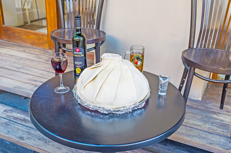 TBILISI, GEORGIA - JUNE 2, 2016: The table in restaurant with bottle of vine, glasses and the dish, covered with a hood, on June 2 in Tbilisi.