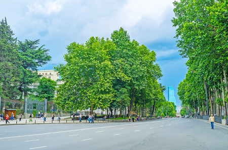 TBILISI, GEORGIA - JUNE 2, 2016: The empty road in Shota Rustaveli Avenue with lush green trees on the both sides, on June 2 in Tbilisi.