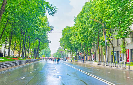 TBILISI, GEORGIA - JUNE 2, 2016: People walk along the wet road in Rustaveli Avenue with lush trees from both sides of the road, on June 2 in Tbilisi.