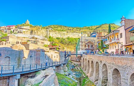 TBILISI, GEORGIA - JUNE 5, 2016: The Fig Gorge in Abanotubani neighborhood with the old Sulfur Baths and Tabor Monastery on the hilltop from the left side and the Orbeliani bathhouse with old quarters from the right, on June 5 in Tbilisi.