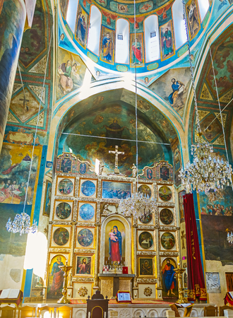 TBILISI, GEORGIA - JUNE 5, 2016: The altar of the Surb Gevorg (St George) Church, the carved wooden iconostasis decorated with icons and surrounded by colorful frescoes, on June 5 in Tbilisi.