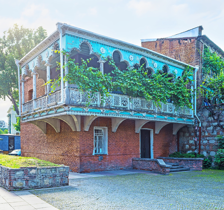 Traditional edifice of old town, decorated with colorful open wooden balcony with pillars, carved patterns and lush grape vines, Tbilisi, Georgia. Stock Photo