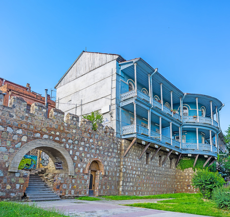 The fortress wall in old Tbilisi and the old mansion, decorated with carved balconies in Kalaubani district, Georgia. Editorial