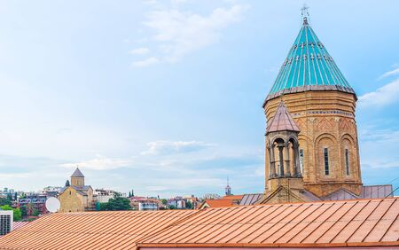 The bright blue dome of Armenian Surb Gevorg (St George) Church, located in Abanotubani neighborhood and the medieval Metekhi church on background, Tbilisi, Georgia. Stock Photo