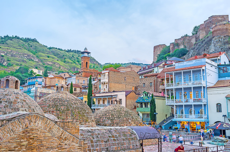 TBILISI, GEORGIA - JUNE 5, 2016: The domes of Sulphur baths are neighboring with historic quarters of Abanotubani district, the colorful townhouses and mansions with open wooden balconies serve as hotels, art galleries and cafes, on June 5 in Tbilisi.