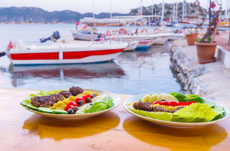 The outdoor port cafe offers tasty turkish dish kofta with view on moored boats, Kekova, Turkey