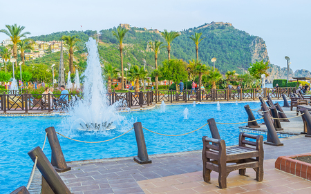 ALANYA, TURKEY - MAY 8, 2017: The coastal Abdurrahman Alaettinoglu park is the perfect place to relax in shade and enjoy the fountains or the Castle, located on the rock, on May 8 in Turkey.