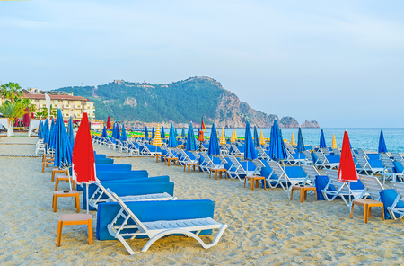 The rows of sun beds and umbrellas on the sandy Kleopatra beach, with the medieval castle on the rocky hill on background, Alanya, Turkey.