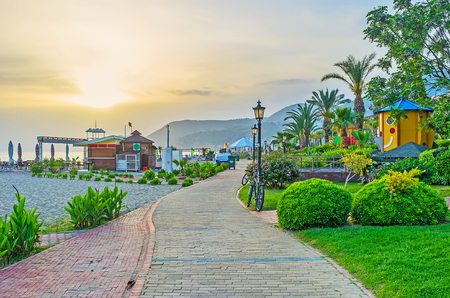 The seaside walk in Alanya with a view on Kleopatra beach and lush green gardens on sunset, Turkey. Stock Photo