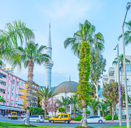 The mosque of Hasan Senli Saray is hidden among the palms and blooming trees of Ataturk boulevard in Alanya, Turkey.